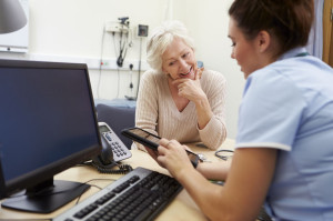 nurse showing an elderly woman something on a tablet in office