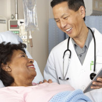 doctor uses tablet with patient