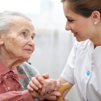nurse holding hand of elderly woman patient