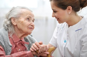 nurse holding hand of elderly woman patient