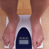 man stands on a scale with diet pills at his feet