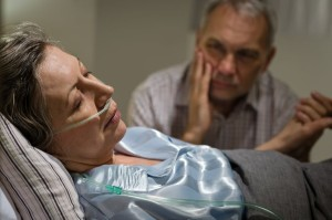 elder woman sick in bed with husband looking on