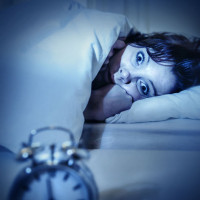 woman staring at the alarm clock in bed