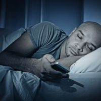 man-in-bed-with-phone-stock