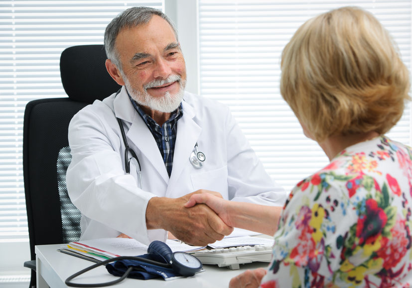 doctor shaking hands with female patient
