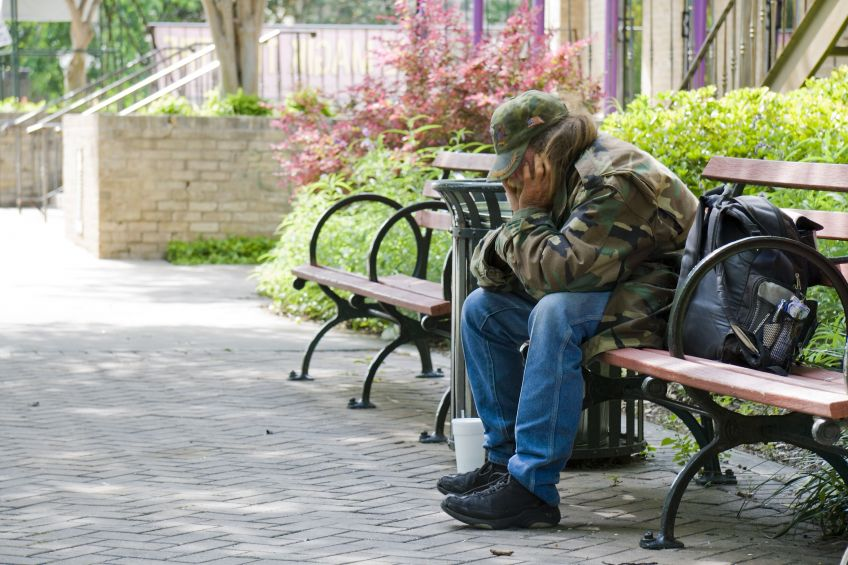 homeless man on a bench wearing an army jacket
