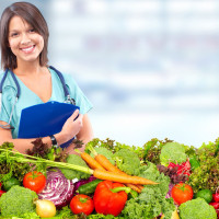 young female doctor standing by pile of produce